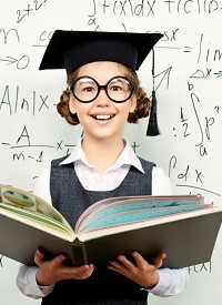 Pretty smart schoolgirl in big glasses and academic hat stands with opened book at the blackboard. Education.